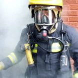 Fire-fighter-wearing-full-breathing-apparatus-and-protective-equipment-after-a-sprinkler-demonstration-exercise-large